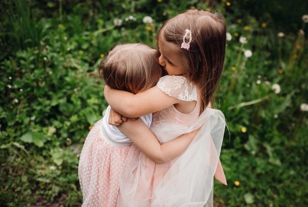 Les petites filles en robes roses courent sur une pelouse verte