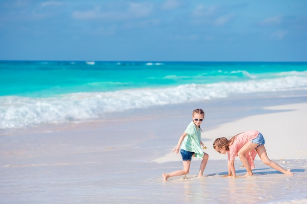 Petites filles s'amusant sur une plage tropicale jouant ensemble à l'eau peu profonde