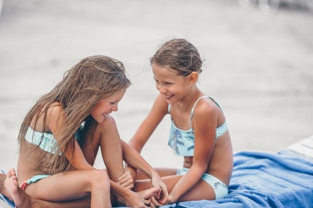 Petites filles s'amusant sur une plage tropicale jouant ensemble