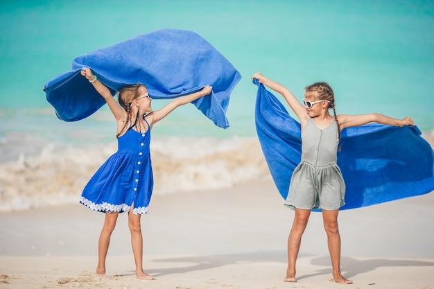 Petites filles s'amusent avec une serviette de plage pendant des vacances tropicales