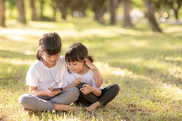 Petites filles sœurs écoutant de la musique avec un casque heureux ensemble