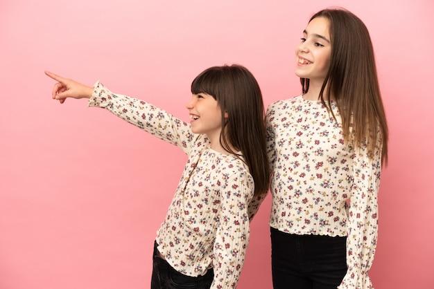 Petites filles sœurs isolées sur fond rose présentant une idée tout en regardant en souriant vers