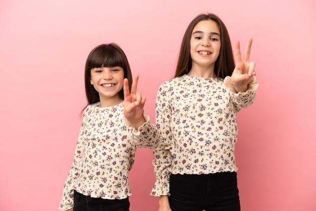 Petites filles sœurs isolées sur fond rose souriant et montrant le signe de la victoire