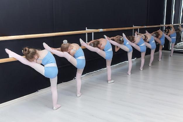 Les petites filles sont engagées dans la classe d'une école chorégraphique
