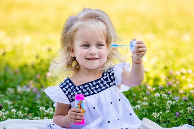 Petites filles soufflent des bulles assis sur l'herbe