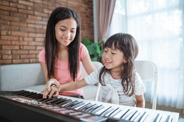Les petites filles avec le sourire jouent un clavier d'instrument de musique