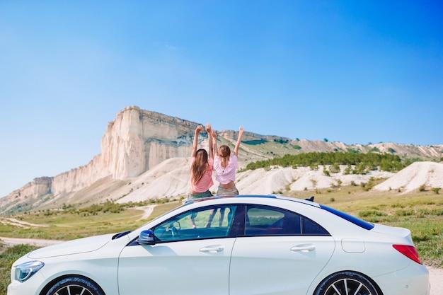 Les petites filles voyagent en voiture en vacances d'été dans les montagnes