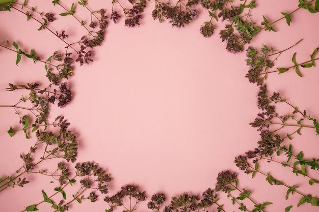 Petites fleurs comme cadre sur fond rose, une place pour une inscription