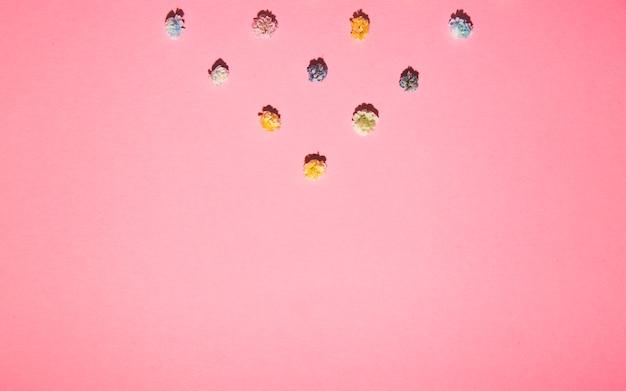 De petites fleurs de gypsophile avec des ombres dures se trouvent géométriquement sur un fond rose.