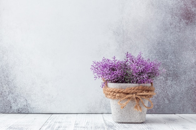 Petites fleurs violettes dans des pots en céramique gris sur fond de pierre style rustique