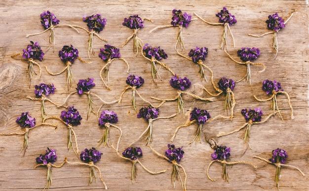 Petites grappes de fleurs sauvages et violettes sur fond en bois ancien, vue de dessus plat poser