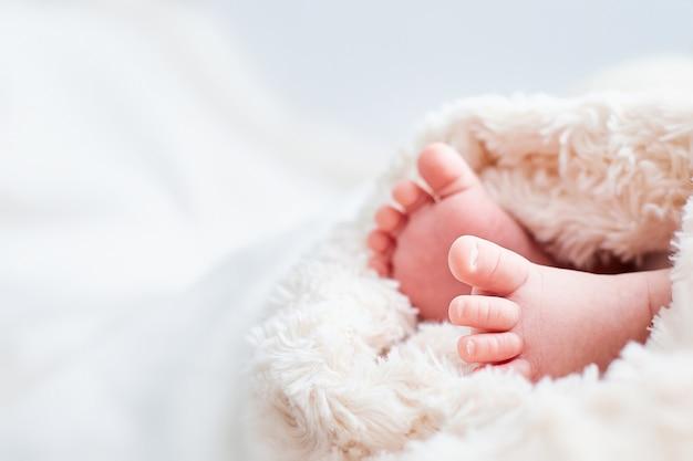 Petites jambes de bébé enveloppées dans un tissu beige. place pour le texte. carte pour enfants.