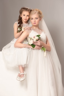 Petites jolies filles avec des fleurs vêtues de robes de mariée