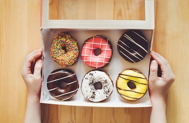 Petites mains d'enfants tenant la boîte avec le dessert de beignets sucrés.