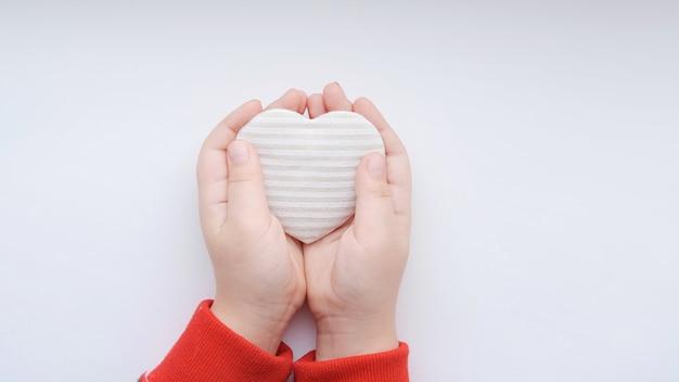 Petites mains de filles tiennent coeur beige rayé de tissu sur fond gris. photo de haute qualité