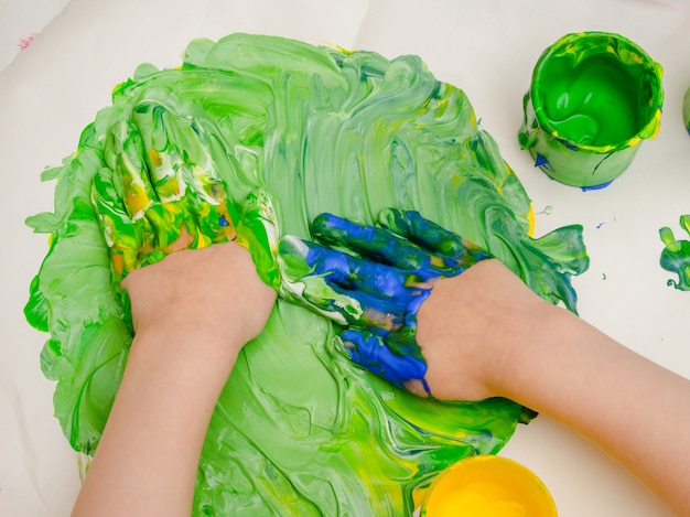 Petites mains jouant avec de la peinture.