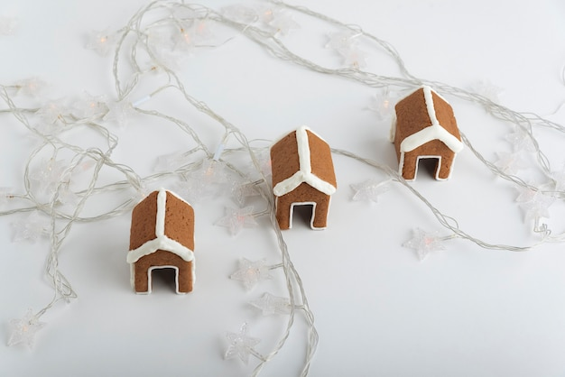 Petites maisons en pain d'épice sur fond blanc et guirlandes de noël. produits de boulangerie de noël.