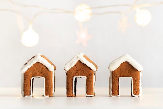 Petites maisons en pain d'épice qui tiennent sur une tasse. biscuits de pain d'épice sur fond de guirlande.