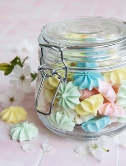 Petites meringues colorées dans le bocal en verre sur fond de tuile rose