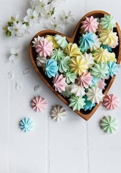 Petites meringues colorées dans le bol en bois en forme de coeur sur fond de carreaux blancs