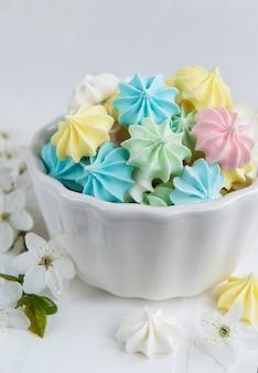 Petites meringues colorées dans le bol en céramique sur fond de carreaux