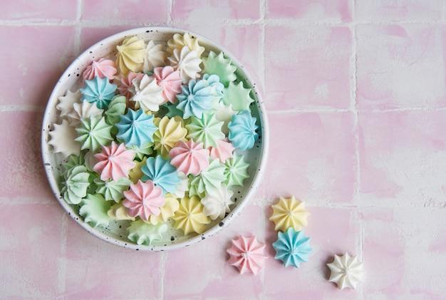 Petites meringues colorées dans le bol en céramique sur la surface des carreaux roses