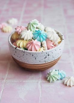 Petites meringues colorées dans le bol en céramique sur la surface des carreaux
