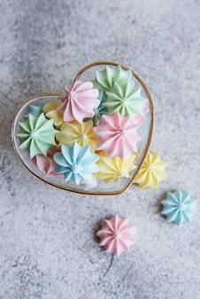 Petites meringues colorées dans le bol en forme de coeur sur fond de béton