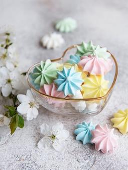 Petites meringues colorées dans le bol en forme de coeur sur une surface en béton