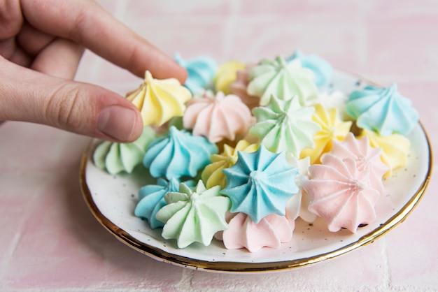 Petites meringues colorées dans la plaque en céramique sur fond de tuile rose