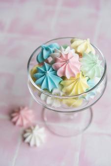 Petites meringues colorées dans le verre sur fond de tuile rose