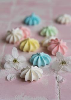 Petites meringues colorées sur fond de tuile rose