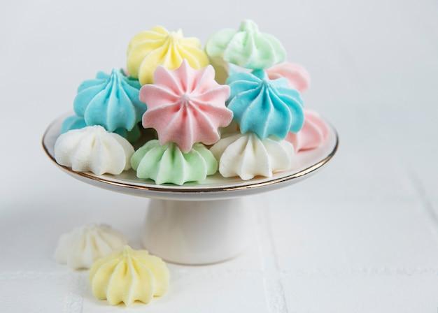 Petites meringues colorées sur le support en céramique sur fond de carreaux