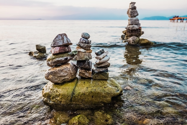 Petites montagnes de pierres en colonnes créées par des touristes au bord d'un lac au coucher du soleil.