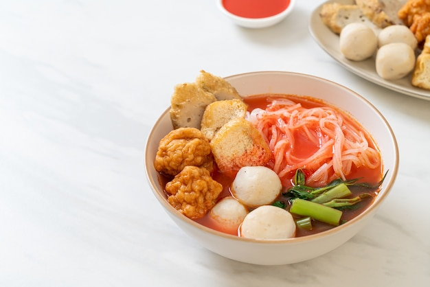 Petites nouilles de riz plates avec des boulettes de poisson et des boulettes de crevettes dans une soupe rose, yen ta four ou yen ta fo - cuisine asiatique