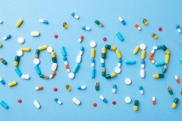Petites pilules de différentes couleurs et formes disposées en mot sur bleu