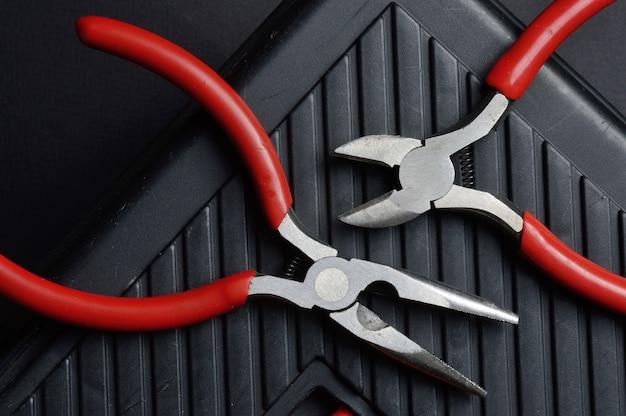 De petites pinces et pinces reposent sur une boîte à outils fermée. vue d'en-haut.