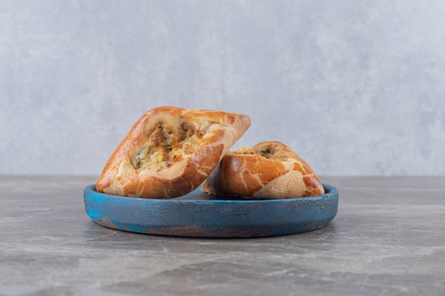 Petites portions de pides turcs turcs sur un plateau bleu sur une surface en marbre