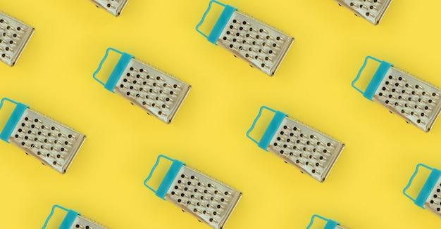 De petites râpes en acier inoxydable reposent sur un papier de couleur pastel.