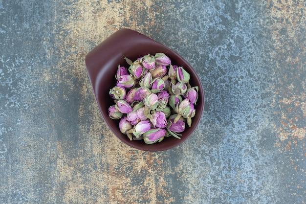 Petites roses en herbe dans un bol sombre.