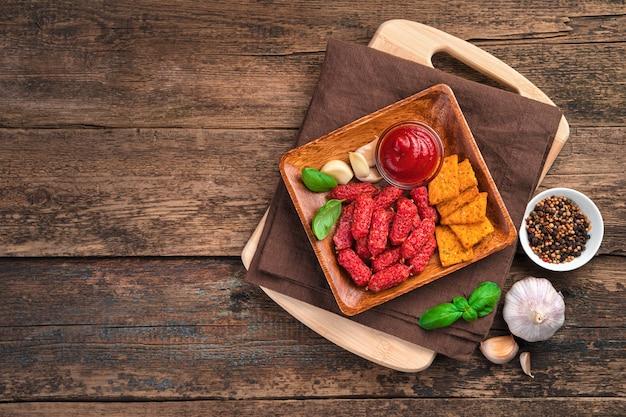 Petites saucisses à l'ail et craquelins aux tomates, basilic et sauce sur un bureau en bois brun. vue de dessus, copiez l'espace.