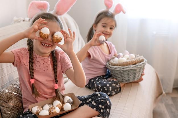 Petites sœurs aux oreilles de lapin, avec des oeufs de pâques à la maison sur le canapé