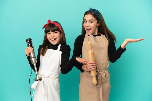 Petites soeurs cuisinant à la maison isolées sur fond bleu avec une expression faciale surprise et choquée