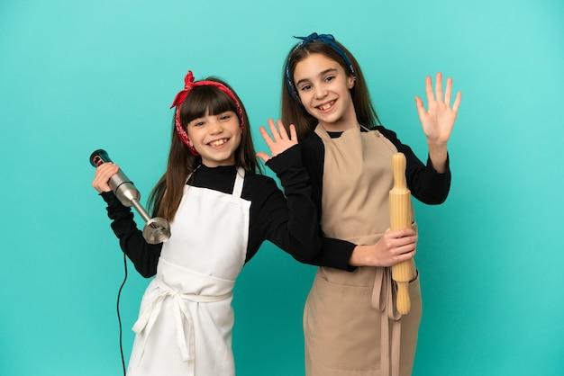 Petites soeurs cuisiner à la maison isolé sur fond bleu saluant avec la main avec une expression heureuse