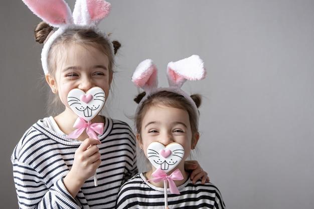 Petites sœurs drôles avec des pains d'épices de pâques en forme de visages de lapin et avec des oreilles de lapin.