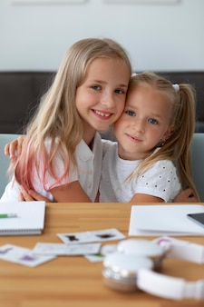 Petites soeurs faisant l'école en ligne ensemble à la maison