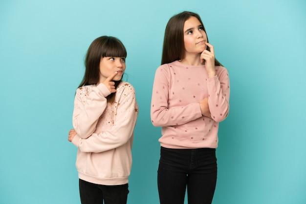 Petites sœurs filles isolées sur fond bleu ayant des doutes tout en regardant