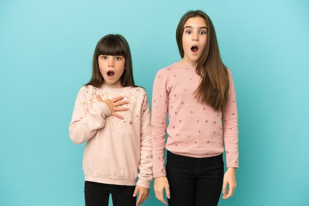 Petites sœurs filles isolées sur fond bleu avec une expression faciale surprise et choquée
