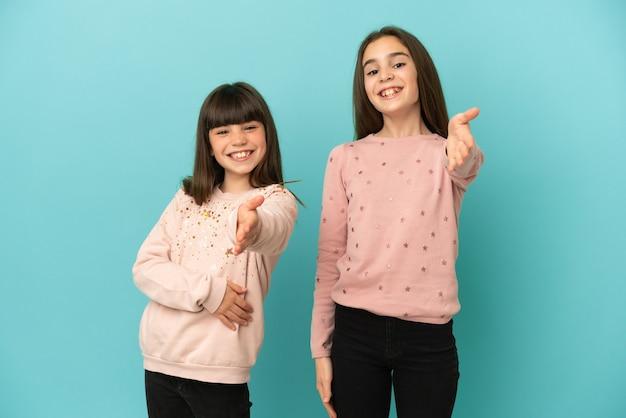Petites soeurs filles isolées sur fond bleu se serrant la main pour conclure une bonne affaire