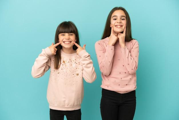 Petites soeurs filles isolées sur fond bleu souriant avec une expression heureuse et agréable